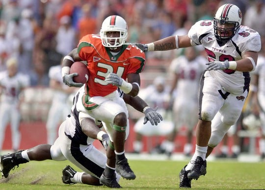 Miami's Phillip Buchanon (31) evades Temple defenders Yazid Jackson, back, and Anthony Nembhard (53) during a punt return that Buchanon ran back for a touchdown in the second half Saturday Nov. 3, 2001 at the Orange Bowl in Miami.