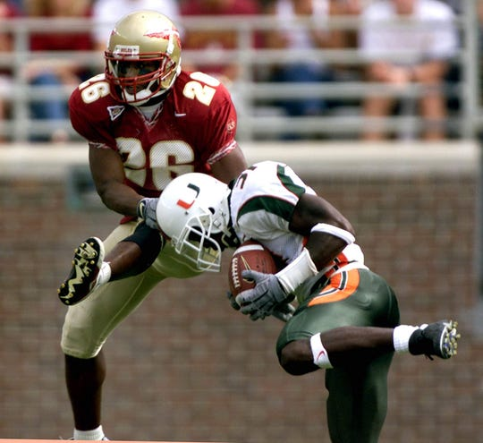 Miami's Phillip Buchanon comes down with an interception in the third quarter as Florida State receiver Atrews Bell (26) attempts to make the catch. Miami defeated Florida State 49-27.