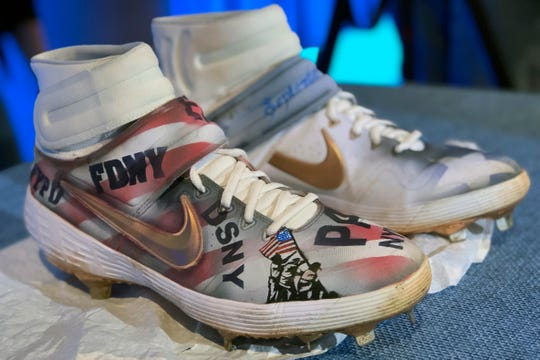 "The custom first-responder cleats New York Mets slugger Pete Alonso used in a game on Sept. 11 are shown at the 9/11 Museum in New York, Tuesday, Oct. 1, 2019. Alonso presented the equipment to museum President Alice M. Greenwald. Alonso said ""it means the world"" that the memorial wanted the gear for its permanent collection. (AP Photo/Jake Seiner)"