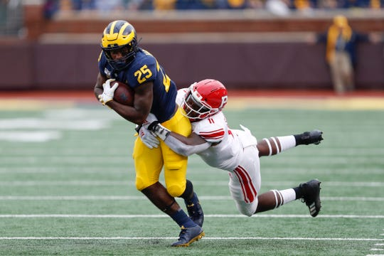 Michigan Wolverines running back Hassan Haskins (25) runs with the ball against Rutgers Scarlet Knights linebacker Drew Singleton (11) in 2019.