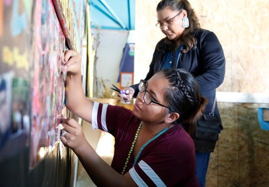 Karrie Sells, bottom, and Shannon Shorthair, both parents in the Family and Child Education program, hang posters on Oct. 1, 2019 in the program's booth for the 108th Northern Navajo Nation Fair at the exhibit hall in Shiprock.