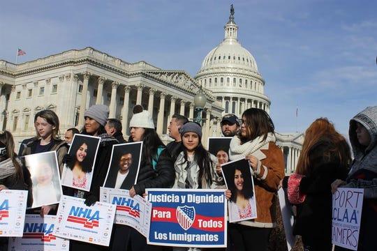 """Varios jóvenes sostienen pancartas que reivindican """"Justicia y dignidad para todos los inmigrantes""""."""