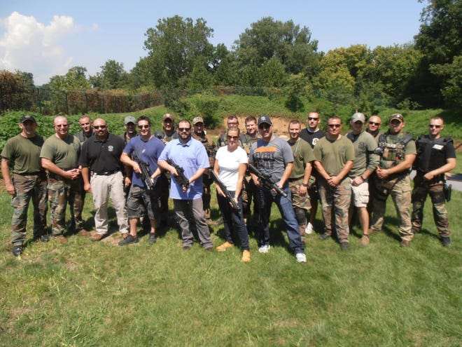 Bill Hynes (front row wearing a gray T-shirt and blue baseball cap) holds a firearm as he and members of the band Live pose with members of the York County Quick Response Team in 2012.