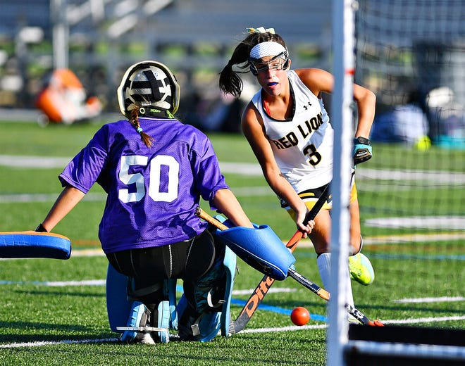 Red Lion's Hannah Downs, right, scores a goal as Central York's Sydney Valdes defends during field hockey action at Horn Field in Red Lion, Tuesday, Oct. 1, 2019. Red Lion would win the game 4-2. Dawn J. Sagert photo