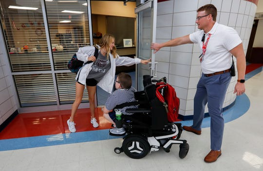 Lilly Wead, left, and Glendale High School Principal Josh Groves hold the door to the main office open for Collin Langston on Tuesday, Oct. 1, 2019.