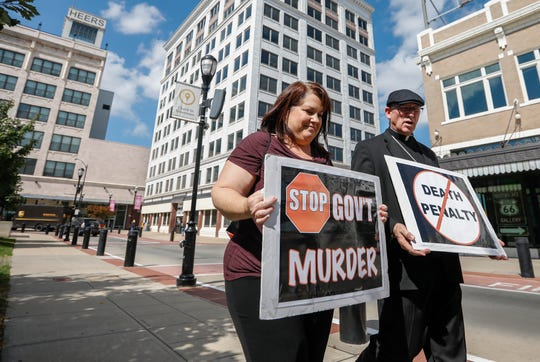 Bishop Edward Rice and Lynn Melendez march around Park Central Square on Tuesday, Oct. 1, 2019, to protest the scheduled execution of Russell Bucklew.