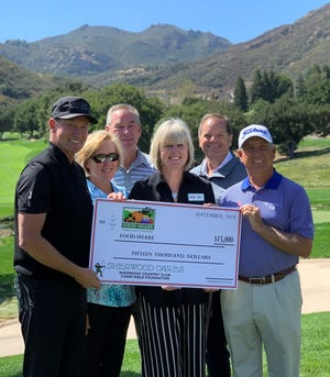 Hockey legend Wayne Gretzky, far left, and PGA Tour Champions player and tournament defending champion Scott Parel, far right, help present a $15,000 check to Food Share President & CEO Monica White, center, during Media Day for the 2019 Invesco QQQ Championship at Sherwood Country Club in Thousand Oaks on Monday.