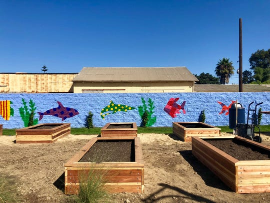 The central courtyard at Ormond Beach villas, a new affordable-housing complex in Oxnard for veterans, includes raised beds for a community garden and a brightly painted mural.