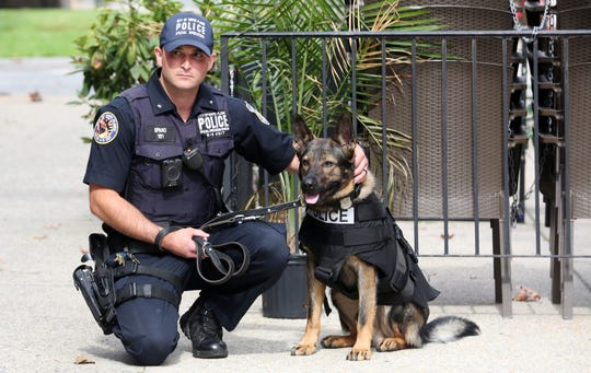 White Plains police K9 officer Steve Spano  and his partner Leo wearing his new bulletproof backpack, during a ceremony outside Berkeley College in White Plains Oct. 1, 2019.   Berkeley College donated the money needed to purchase the bulletproof canine backpacks.