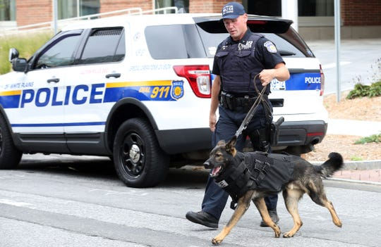 White Plains police K9 officer Brian Johnson and his partner Mickey, wearing his new bulletproof backpack, arrive for a ceremony outside Berkeley College in White Plains Oct. 1, 2019.  Berkeley College donated the money needed to purchase the bulletproof canine backpacks.