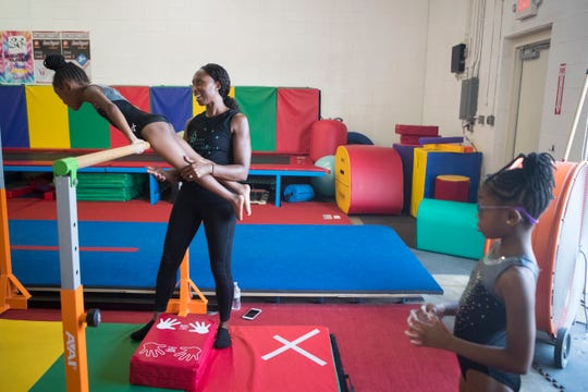 Monet Tillman Horsey, left, helps a student through a exercise during class Wednesday, Sept. 4, 2019 at Dream Chasers Gymnastics.