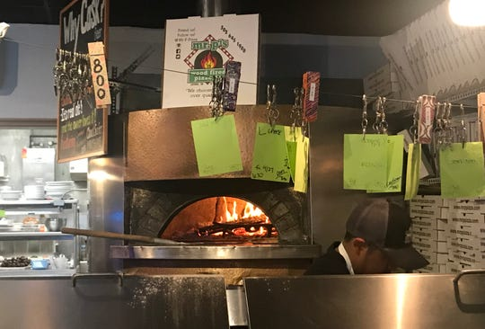 Call-ahead orders hang from a clothes line near Italian-made wood-fired pizza oven at Mr. P's in Lewes.