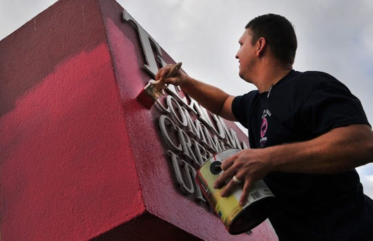 "Wichita Falls firefighter, Jonathan Bradley helps paint the large ""T"" sign, Tuesday morning located at the credit union's Southwest Parkway branch for Breast Cancer Awareness Month."