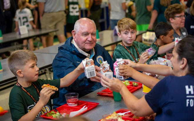 U.S. Secretary of Agriculture Sonny Perdue enjoys a milk toast with Sugar Creek Elementary students Jameson, left, Elliot and dairy farmer Marilyn Hershey, right, on Tuesday, Oct. 1, 2019 in Verona, Wis.