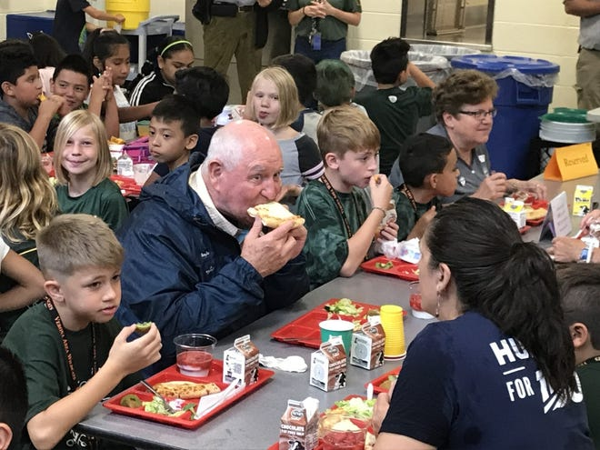 U.S. Ag Secretary Sonny Perdue enjoys a slice of pizza topped with Wisconsin cheese during lunch with students at Sugar Creek Elementary School in Verona, Wis., on Oct. 1, 2019.