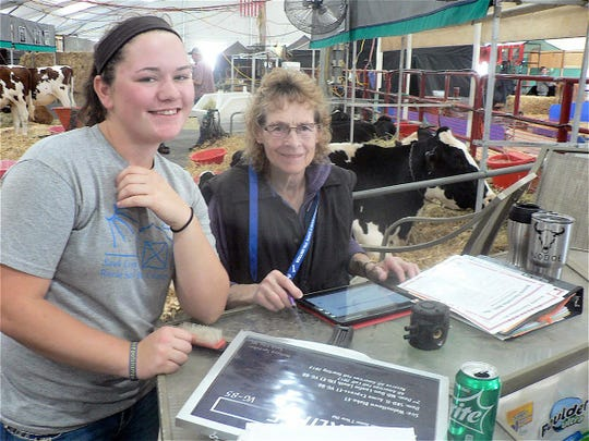 Barb Kayser, Milton checks the pedigrees shown by Melissa Sprecher of Sauk City who is taking care of the cattle owned by Matt and Kate Smith, Reedsburg.