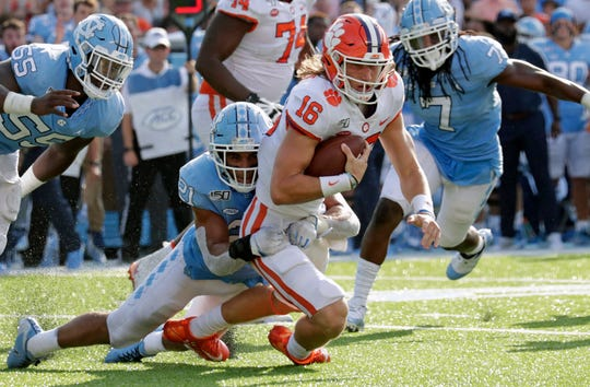 Clemson quarterback Trevor Lawrence is stopped by North Carolina's Chazz Surratt during the first half at Kenan Stadium.