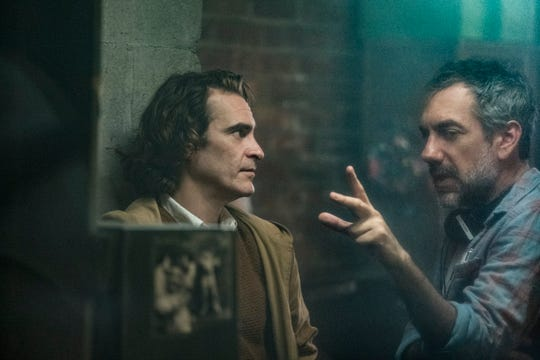 "Joaquin Phoenix (left) goes over a scene with director Todd Phillips on the set of ""Joker."""