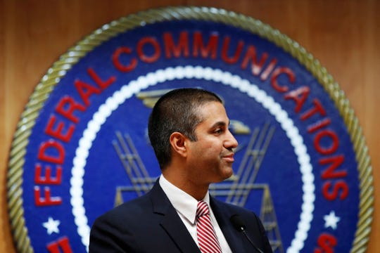 In this Dec. 14, 2017, file photo, after a meeting voting to end net neutrality, Federal Communications Commission (FCC) Chairman Ajit Pai smiles while listening to a question from a reporter in Washington.
