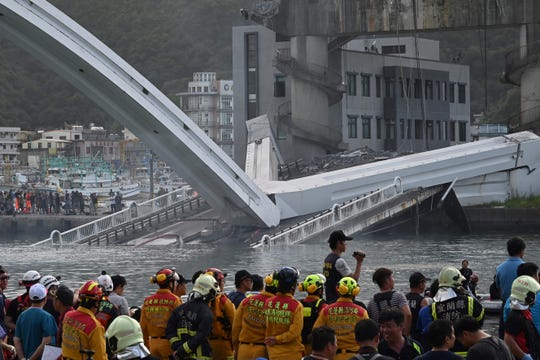 Rescue personnel look on at a bridge after it collapsed in the Nanfangao fish harbor in Suao township on Oct. 1.