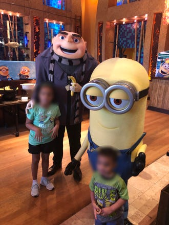 """In this photo provided by the Zingers, a Universal Orlando employee dressed as Gru from """"Despicable Me"""" makes an """"OK"""" symbol on their daughter's shoulder."""