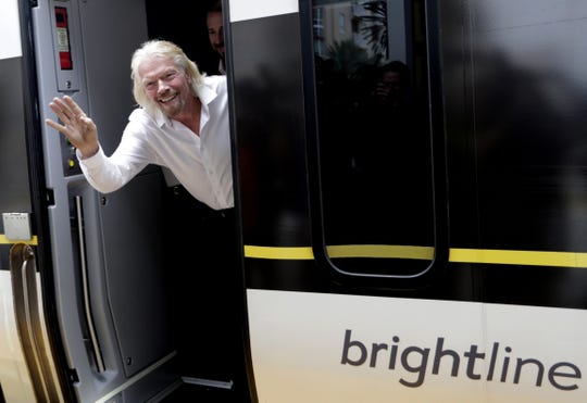 FILE - In this April 4, 2019, file photo Richard Branson, of Virgin Group, waves as he arrives on a Brightline train in West Palm Beach, Fla. Branson has taken as he's gone from owning the Virgin record label to planning space flights have been an inspiration for Elizabeth Babinski in her wedding business. (AP Photo/Lynne Sladky, File)