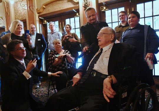 Robert Holladay, center, regales friends and those recording Tuesday's portrait unveiling with stories and movie trivia after his likeness was unveiled at the Paramount Theatre.
