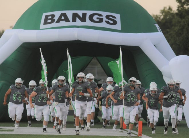 The Bangs football team runs onto the field before a game against Anson on Friday, Sept. 27, 2019, at Dragon Memorial Stadium in Bangs.