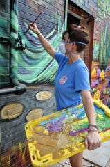 Calina Mishay Johnson uses a storage tub lid as a palette to blend colors while working on a new mural by the back entrance to The Local on Tuesday.