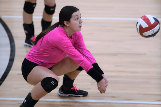 Abilene High libero Maddie Perez (3), wearing a pink shirt, reaches to return a serve against Weatherford at Eagle Gym on Oct. 1.