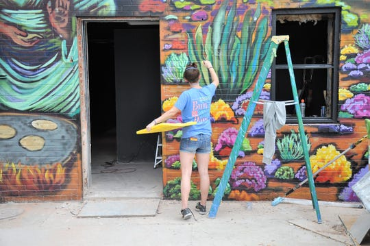 Calina Mishay Johnson works on a new mural by the back entrance to The Local.