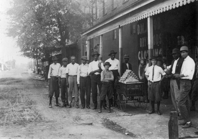 L.B. Jackson pictured with his brother and customers in a Jackson family photo.