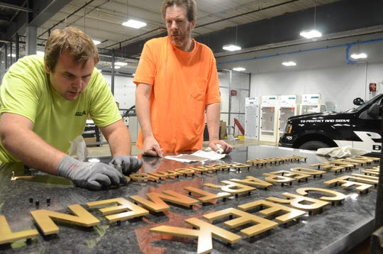 Alex Robertson, left, and Scott Hulce of Sweitzer Construction work on the memorial plaque earlier this year.