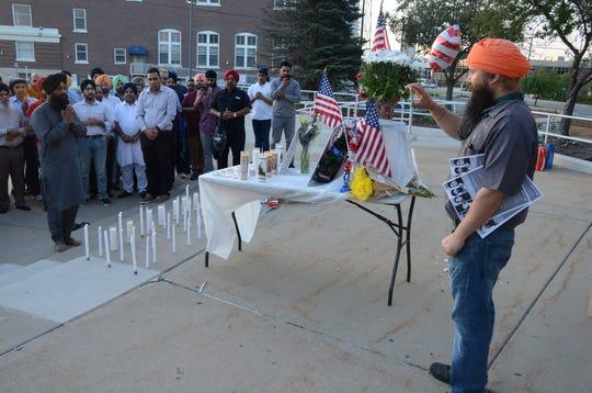 Sonny Singh of Battle Creek photographs the memorial service  for Deputy Sandeep Dhaliwal, killed last week in Texas.