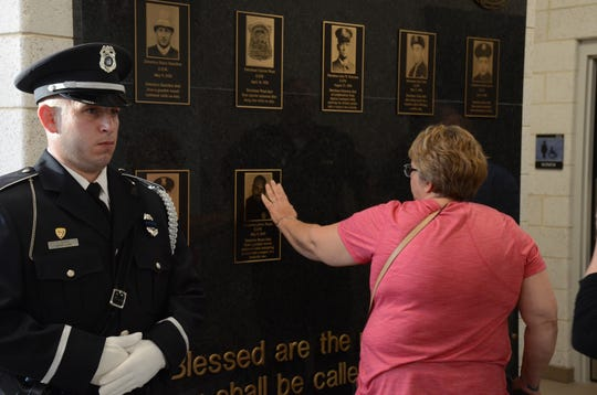 As Officer Thomas Burke, a member of the honor guard stands, Melanie Brann touches the memorial to her husband, Det. Lavern Brann, who was killed in 2005.