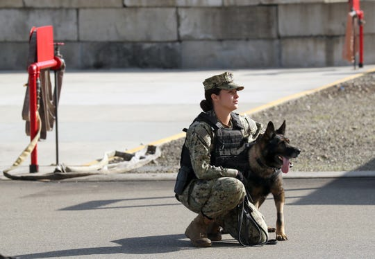 Naval Base Kitsap Bangor's Petty Officer 3rd Class Paulina Palazuelos, Master-at-Arms, and K-9 Turbo await their turn to run a scenario in the fire tower at the Bremerton Readiness Center during the Washington State Police Canine Association's 2019 Fall Seminar.