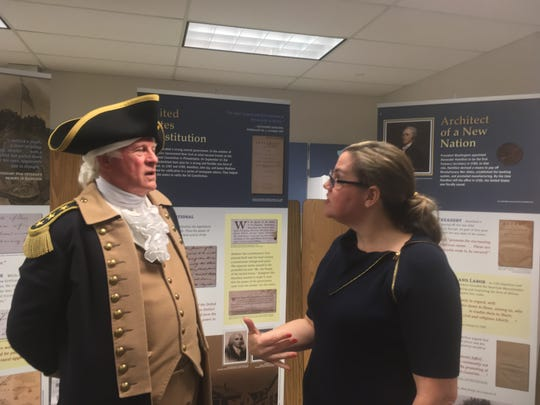 George Washington portrayed by Vern Frykholm of Sequim discusses U.S. history with Mountain View Middle School teacher Anne Pedelaborde in front of a traveling exhibit on Alexander Hamilton on loan to the school from the Gilder Lehrman Institute of American History on Oct. 1, 2019.