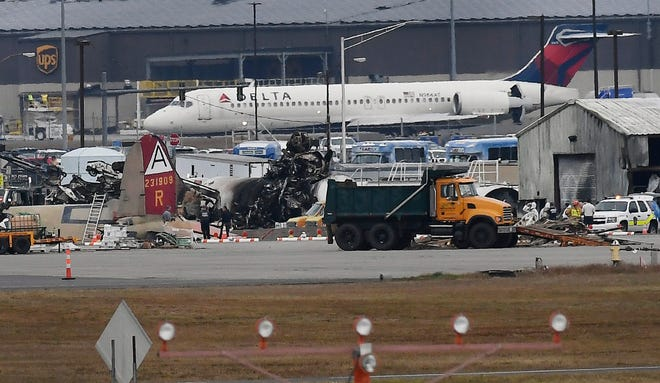 A Delta commercial airline plane taxis to take-off behind investigators at the wreckage of World War II-era bomber plane that crashed at Bradley International Airport in Windsor Locks, Conn., Wednesday,
