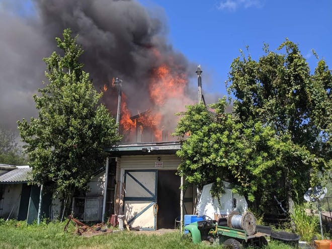Flames leap from the second story of a large barn Wednesday afternoon in Titusville.