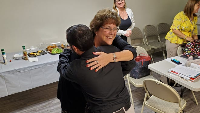 District negotiator Karyle Green and BFT President Anthony Colucci embrace after reaching a deal on raises for the 2019-20 teacher contracts.