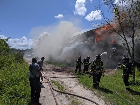 Firefighters converge on a large burning barn Wednesday afternoon off Fox Lake Road in Titusville.