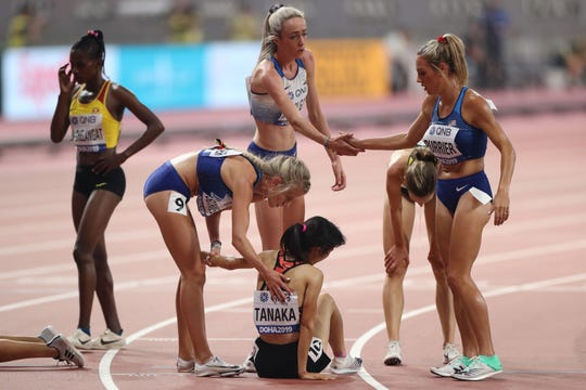 USA's Karissa Schweizer (2nd L) helps Japan's Nozomi Tanaka (C), as Britain's Eilish Mccolgan (back C) shakes hands with USA's Elinor Purrier (R) after the Women's 5000m heats at the 2019 IAAF Athletics World Championships at the Khalifa International stadium in Doha on October 2, 2019. (Photo by ) (Photo by KARIM JAAFAR/AFP via Getty Images)