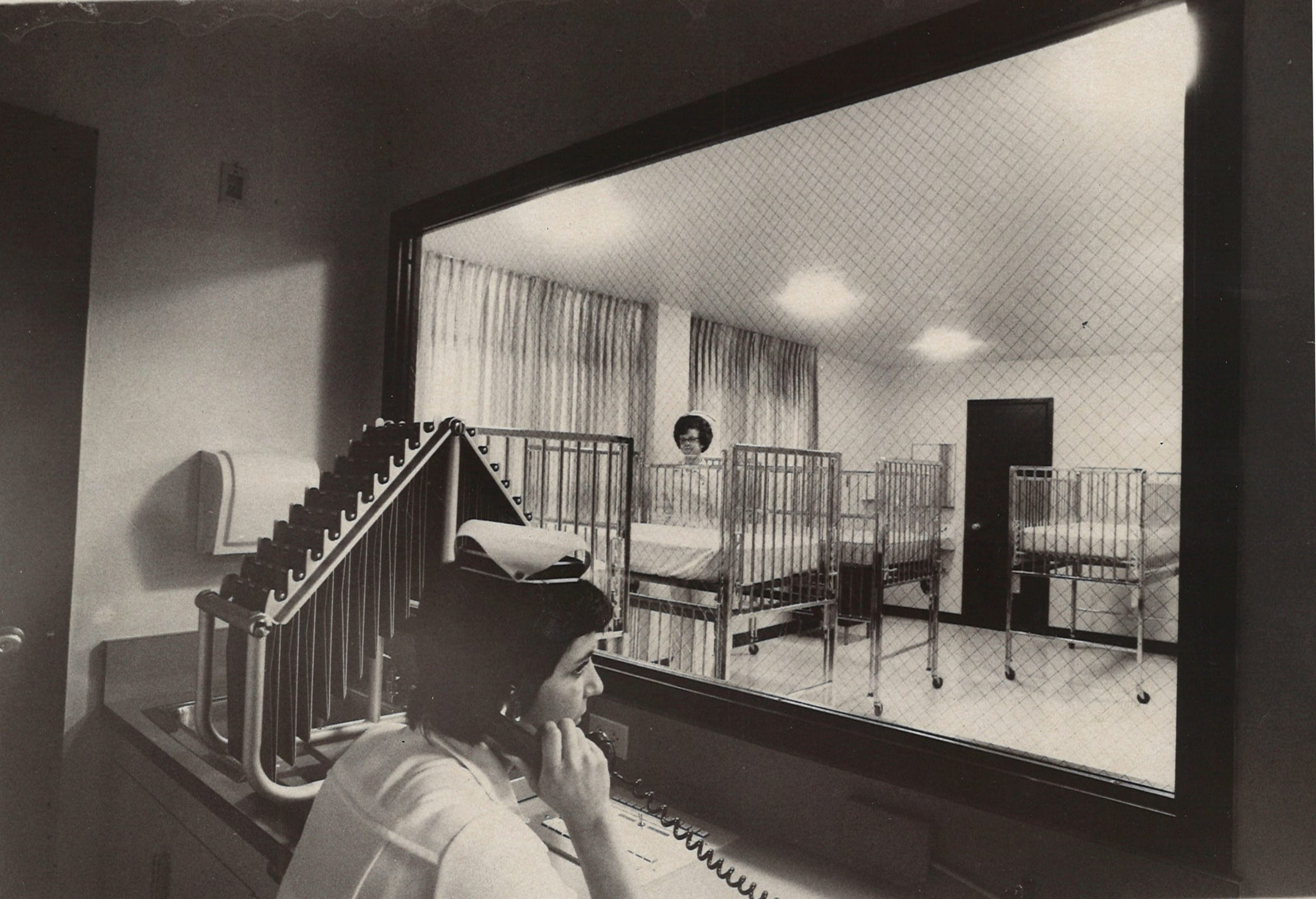 Nurse Irma Lopez speaks on the phone in the nurses station as Lela Shumate sets up cribs in the nursery of Corpus Christi Osteopathic Hospital in October 1975 on Tarlton Street in Corpus Christi. The hospital had just completed an addition, making it the third largest hospital in Corpus Christi at the time.