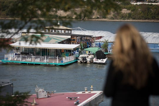 A pedestrian looks on as Emergency personnel investigate on the Ludlow Bromley Yacht Club bar as it is adrift in the Ohio River after a barge struck the Ludlow Bromley Yacht Club  in Ludlow, Ky., on Wednesday, Oct. 2, 2019.