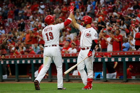 Cincinnati Reds first baseman Joey Votto (19) and third baseman Eugenio Suarez (7) high five after Votto's solo home run in the third inning of the MLB National League game between the Cincinnati Reds and the Pittsburgh Pirates at Great American Ball Park in downtown Cincinnati on Tuesday, July 30, 2019.