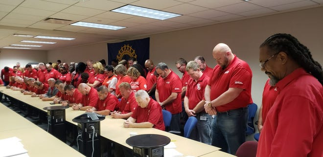 """The UAW's elected bargaining committee stand """"solidarity strong"""" at the main bargaining table where they are negotiating with General Motors bargainers for a new tentative agreement."""