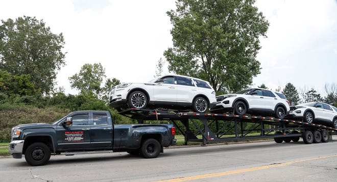 Two Ford Explorers and one Lincoln Aviator are seen on a car hauler on Gibraltar Road near Ford's Flat Rock Assembly Plant in Flat Rock last month. Flat Rock is among the plants Ford has committed investments to as part of its agreement with the UAW.