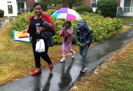 Betty Kabbashi, a medical interpreter, takes her children, Roda, 5, center, and Richie, 7, to school in the rain on Tuesday, Oct. 1, 2019, in South Portland, Maine. Kabbashi, who was a dentist in South Sudan, disagrees with President Trump's plan to further cut refugee quotas.