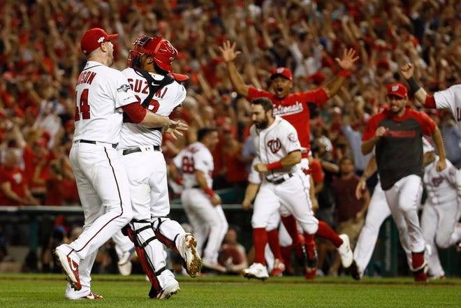 Washington Nationals relief pitcher Daniel Hudson, left, and catcher Kurt Suzuki celebrate with teammates after closing out a National League wild-card baseball game against the Milwaukee Brewers, Tuesday in Washington. Washington won 4-3.
