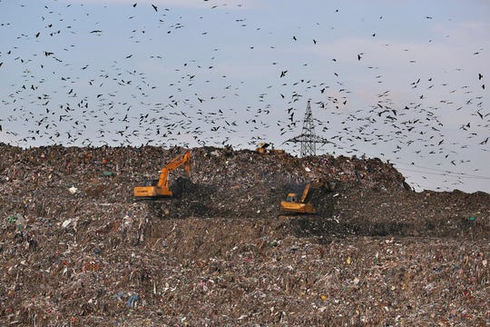 "In this Thursday, Sept. 26, 2019 photo, land movers work on a mountain of garbage in the outskirts of New Delhi, India. Environment ministry official Chintan Mishra says efforts to ""sensitize"" the public against single-use plastics started Wednesday, the 150th anniversary of independence leader Mohandas Gandhi's birth."